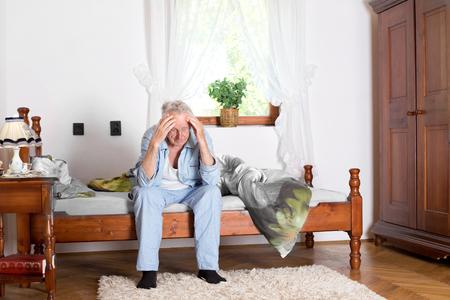 caras tristes: Anciano sentado en la cama y sosteniendo la cabeza con las manos