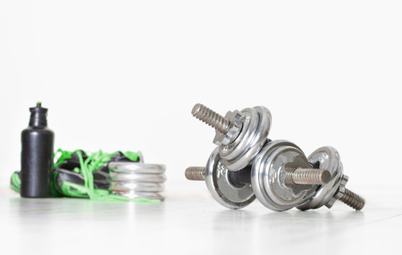 additional training: Sport concept. Close up of two steel dumbbells and green sneakers and bottle of water in background Stock Photo