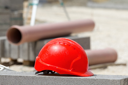 red hat: Red helmet standing on concrete roadside at construction site. Plastic pipes and roadside blocks in background