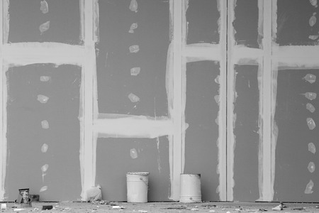 Front view of gypsum wall with joints at building site. Black and white image Standard-Bild