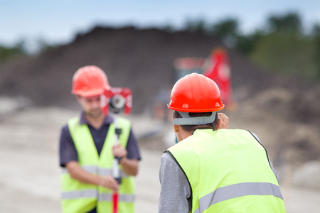 Surveyor engineers working with theodolite on road construction site