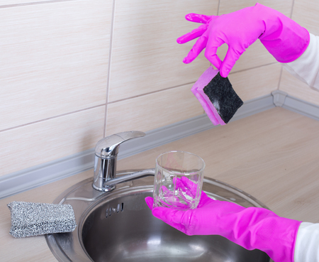 Woman holding dirty glass and sponge for dish washing with two fingers. Feeling displeased and disgusted Stock Photo