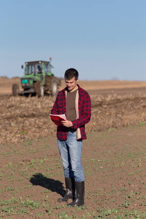 landowner: Young handsome farmer standing on farmland. Tractor working in background. Vertical composition on image