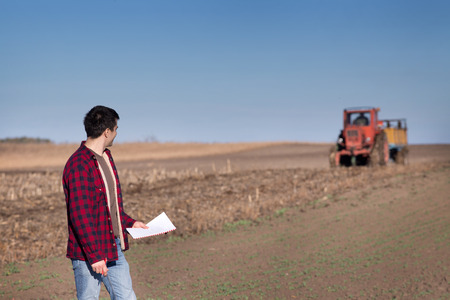 fertile land: Young handsome farmer standing on farmland. Tractor working in background