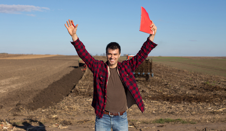 raised arms: Young excited farmer standing on farmland with raised arms. Tractors working in background
