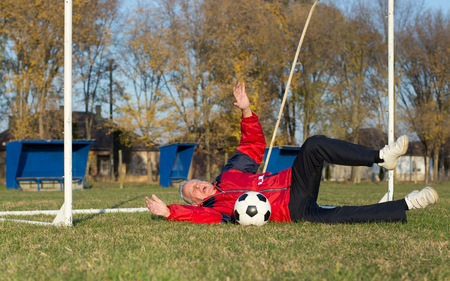 the seventies: Old man in seventies falling down on grass when trying to catch a soccer ball on goal on playground