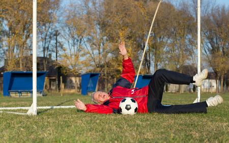 hombres maduros: Viejo hombre en setenta caer sobre la hierba al intentar atrapar un balón de fútbol a puerta en el patio Foto de archivo