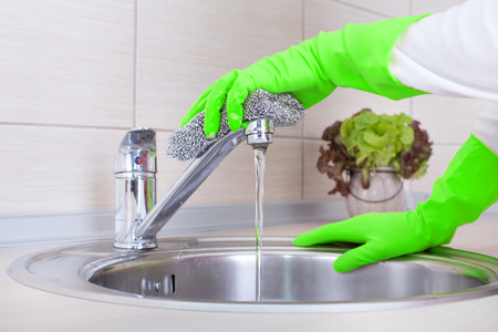 scrubbing up: Close up of female hands with protective gloves scrubbing and cleaning kitchen faucet Stock Photo