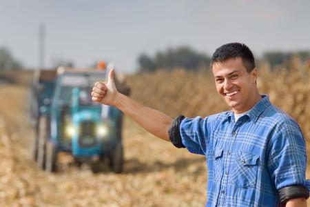 granjero: Granjero sonriente joven que muestra el pulgar para arriba como muestra aceptable en las tierras agrícolas. Tractor con remolque en el fondo