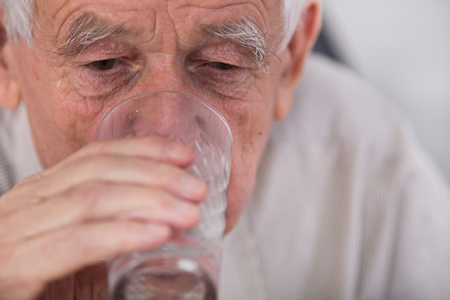 sediento: Cerca del hombre de edad bebiendo agua de vidrio