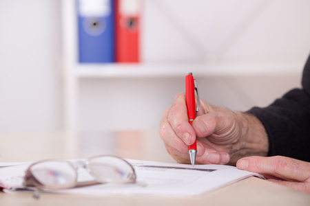 financial official: Close up of senior businessmans hand writing notes with red pencil on the desk in the office