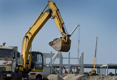 earth moving equipment: Excavator moving earth at construction site. Building development in background