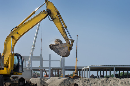 crane bucket: Excavator moving earth at construction site. Building development in background