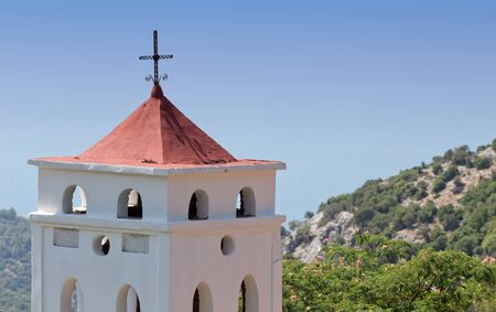 orthodox church: View of greek orthodox church belfry with cross on the roof. Rocky mountains and blue sky in background