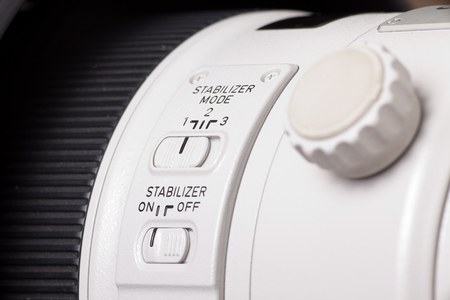 tele up: Close up of function buttons on modern white telephoto lens