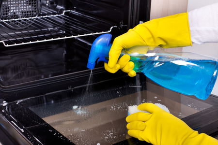 Cerca de la mano femenina con guantes de protección amarillas pulverización de detergente de la botella en la puerta del horno
