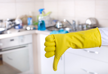 messy kitchen: Conceptual image of kitchen cleaning. Close up of human hand with yellow rubber glove showing thumb down sign. Messy kitchen countertop in background
