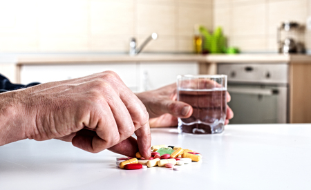 Close up of male hand taking pills from a pile on the white table in kitchen. Holding glass of water