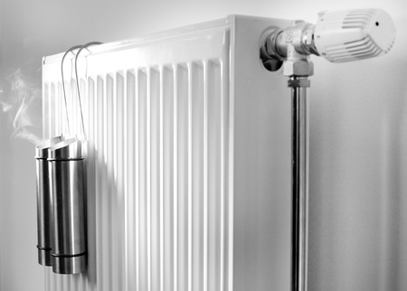 Water evaporation from metal containers on radiator. Concept of good indoor climate in winter season. Black and white image