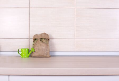 Small sack with green ribbon and small decorative water pot on wooden kitchen countertop