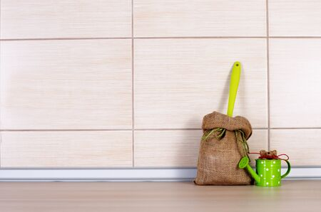 Small sacks with green scoop and small decorative water pot on wooden kitchen countertop