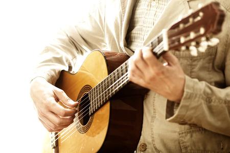 Homme en costume de velours jouer de la guitare classique isolé sur fond blanc