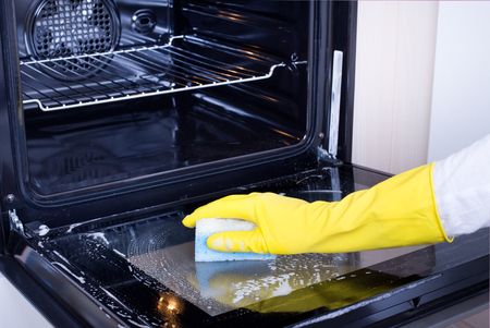 Close up of female hand with yellow protective gloves cleaning oven door Reklamní fotografie - 50443285
