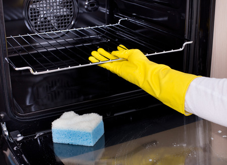 Primo piano della mano femminile con guanti gialli di pulizia del forno Archivio Fotografico - 50443286
