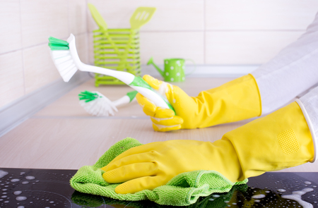 hob: Close up of human hands with protective gloves cleaning induction hob and holding scrubbing brush