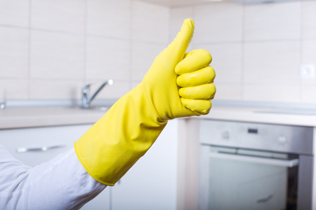 cleaning crew: Conceptual image of home cleaning. Close up of human hand with yellow rubber glove showing ok sign with thumb up. Clean kitchen countertop and furniture in background Stock Photo