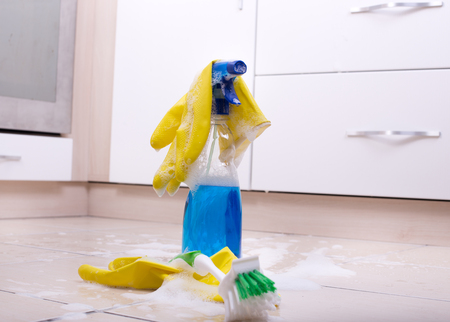 anti bacterial soap: Cleaning supplies on the kitchen floor with foam around them Stock Photo