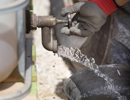 Primo piano della mano di operaio edile il rubinetto versando acqua nel secchio per betonaggio Archivio Fotografico - 51562607