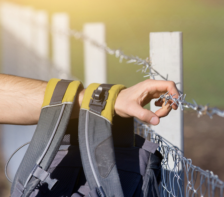 unwelcome: Close up of male hand with backpack holding barbed wire fence Stock Photo