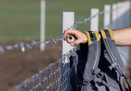 bigotry: Close up of male hand with backpack holding barbed wire fence Stock Photo