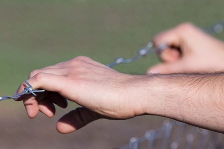 unwelcome: Close up of male hands holding barbed wire fence and begging for help