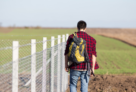bigotry: Young man with head down and backpack on the shoulder walking beside wire fence. Rear view of man Stock Photo