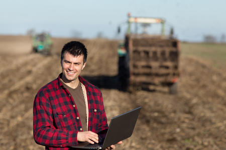 landowner: Portrait of young handsome farmer  with laptop on farmland. Tractors working in background