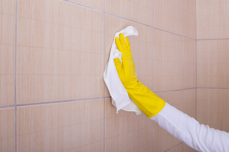Close up of female hand wiping bathroom tiles with white cleaning cloth
