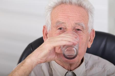 tomando refresco: Hombre mayor de agua potable y mirando a c�mara