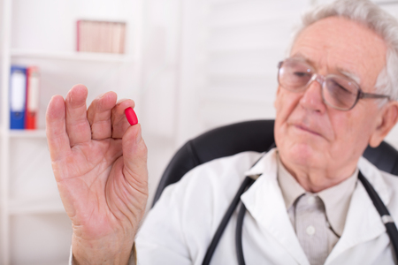 pharmacologist: Senior doctor holding and looking at red tablet in his office