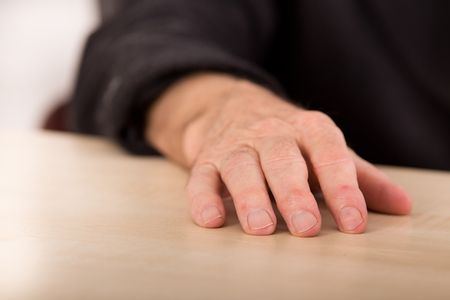 gerontology: Close up of old man wrinkled hand resting on the table