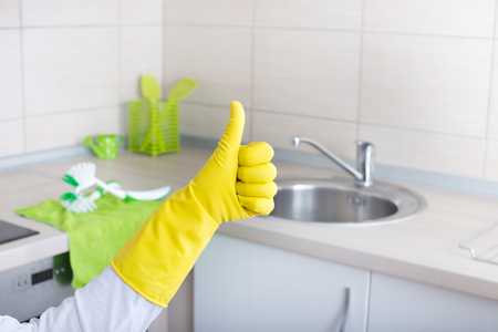 cleaning crew: Conceptual image of home cleaning. Close up of human hand with yellow rubber glove showing ok sign with thumb up. Clean kitchen countertop and rag with brushes on it Stock Photo