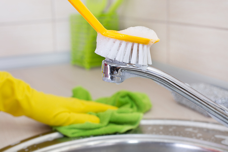 scrubbing up: Close up of scrubbing brush on the kitchen faucet. Kitchen cleaning concept