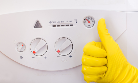 reducing: Close up of human hand showing ok sign with thumb up in front of gas boiler. Energy efficiency and cost reducing concept Stock Photo