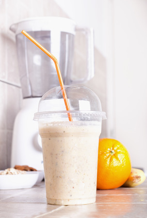 plastic cup: Close up of orange smoothie in plastic cup with straw on kitchen countertop with blender and fruits in background Stock Photo