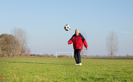the seventies: Happy old man in seventies kicking a soccer ball on the grass field