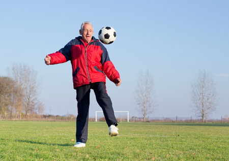 the seventies: Old man in seventies kicking a soccer ball on playground Stock Photo