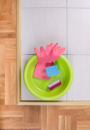 washbasins: Top view of plastic basin with clening tools on tiled floor