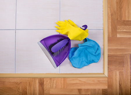 brooming: Top view of dustpan, brush, protective gloves and cloth on tiled floor