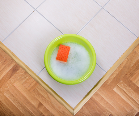 washbasins: Top view of plastic washbasin with foam and sponge on tiled floor